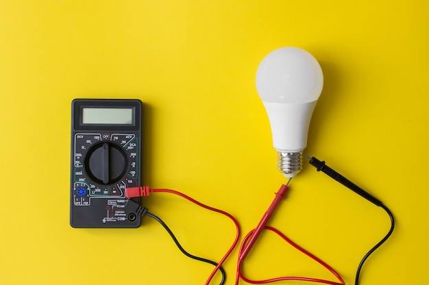黄色の背景にプローブとled電球を備えたダークデジタルマルチメータ。節電コンセプト