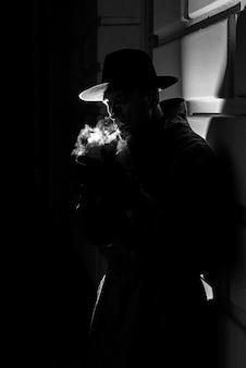 느와르 스타일로 밤에 거리에서 담배를 피우는 모자를 쓴 남자의 어두운 극적인 실루엣