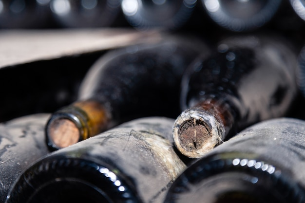 Dark dusty wine bottles with old crumbly cork