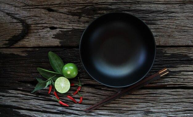 木製のテーブルの上に食べ物の暗い空のボウル