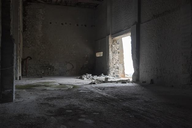 ひびの入ったコンクリートの壁と開いた出入り口からの光の暗い空の倉庫の内部