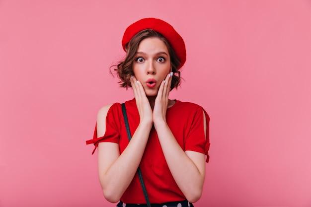 驚きを表現する暗い目のフランス人女性。赤いベレー帽で驚いた魅力的な女の子の肖像画。