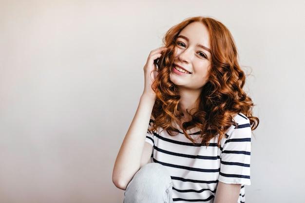 Signora dello zenzero dagli occhi scuri che si siede e che ride. tiro al coperto di una magnifica ragazza caucasica in maglietta a righe.