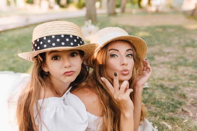 緑豊かな公園で家族の週末を楽しんでいるお母さんと浮気している帽子をかぶった暗い目の女の子。優雅な女性は、変な顔をして、屋外で休んでいる娘と冗談を言っているエレガントなリングを身に着けています。