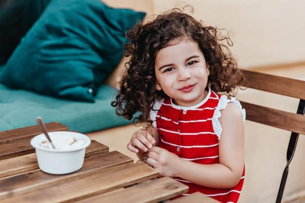 카페에서 디저트를 즐기면서 포즈를 취하는 검은 눈의 아이. 아이스크림을 먹고 웃는 어린 소녀의 야외 사진.