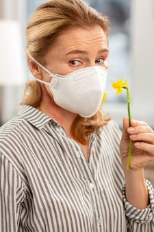 Dark eyed mature woman wearing mask on face having allergy to flowers