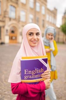 검은 눈의 이슬람 여성. 대학 근처에 서있는 영어 책을 들고 어두운 눈동자 이슬람 여자를 전송