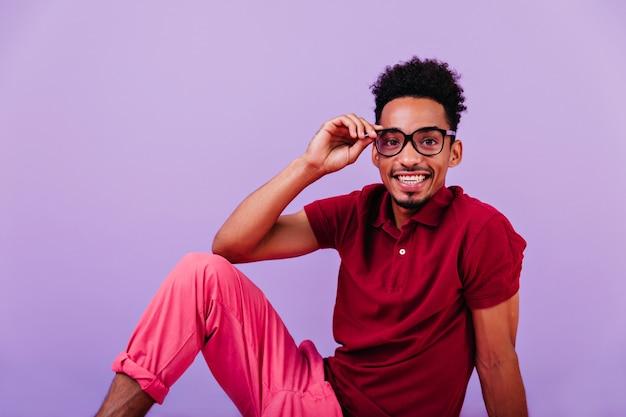 暗い目の前向きな男が笑っています。眼鏡をかけてポーズをとる楽観的なアフリカの少年。