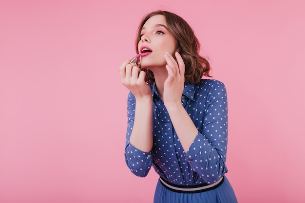 Dark-eyed pretty european lady doing makeup with mouth open. pleasant curly girl in blue clothes using pink lipstick.