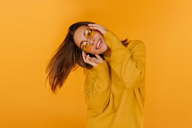 笑っている暗い目の洗練された女の子。黄色い壁に喜んで踊る魅力的なヨーロッパの女性。
