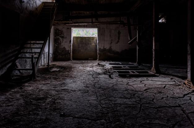 床にひびの入った土が壊れた木製の階段と機械の残骸がある暗い工場の部屋