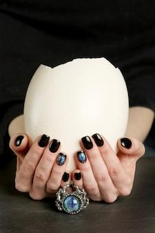 Dark fantasy nail art on manicured hands close-up