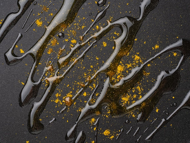 Dark food background with curry spices, oil on fluoroplastic frying pan, macro, close-up, top view