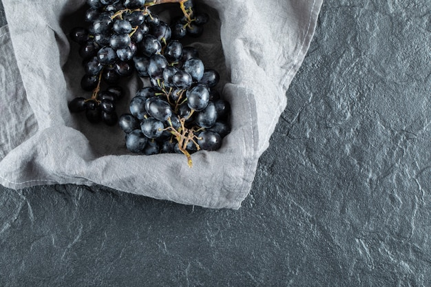 Dark fresh grape in basket on gray tablecloth.