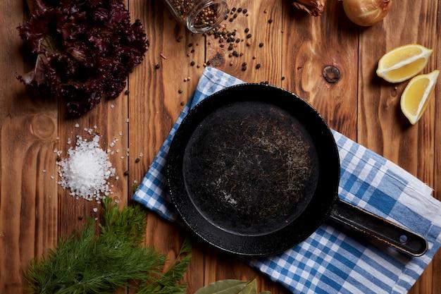 Темная сковорода на деревянной поверхности, приготовление мяса на гриле, украшение рецепта приготовления