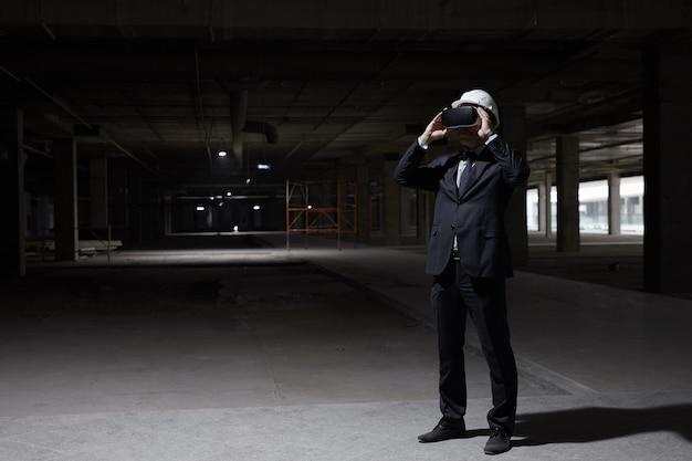 미래의 프로젝트를 3d로 시각화하면서 건설 현장에서 vr 장비를 착용 한 사업가의 어두운 전체 길이 초상화,