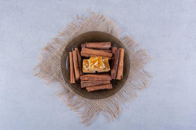 Ciotola di vetro scuro di bastoncini di cannella e caramelle alle noci sul tavolo di pietra.