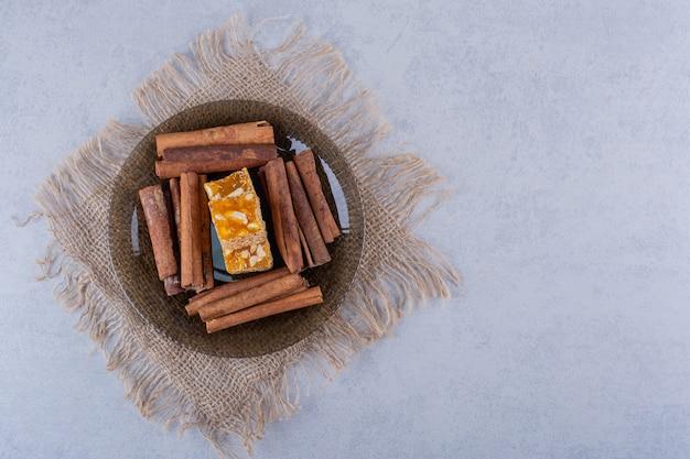 Темная стеклянная миска с палочками корицы и ореховыми конфетами на каменном столе.