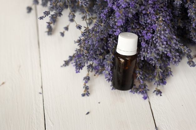 A dark glass jar of lavender essential aromatic oil stands in a purple bouquet of flowers. top view