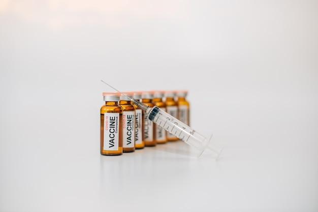 흰색 배경에 복사 공간이 있는 레이블과 바늘이 달린 의료 주사기가 있는 어두운 유리 백신 약병. 의약품 광고 이미지, 선택적 초점.