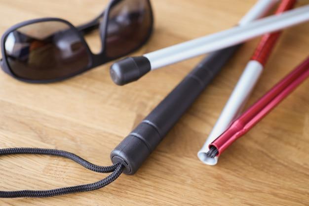 На столе темные очки и палки для слепых