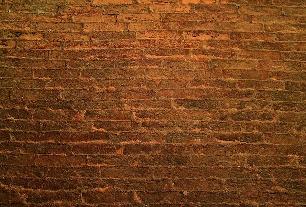 背景のダークゴールデンブラウングランジレンガの壁