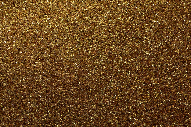 Dark golden sparkling background from small sequins, closeup. brilliant backdrop.