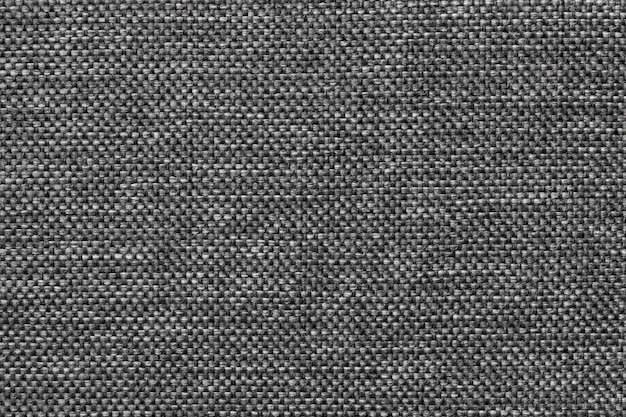 Dark gray background of dense woven bagging fabric, closeup. structure of the textile macro.