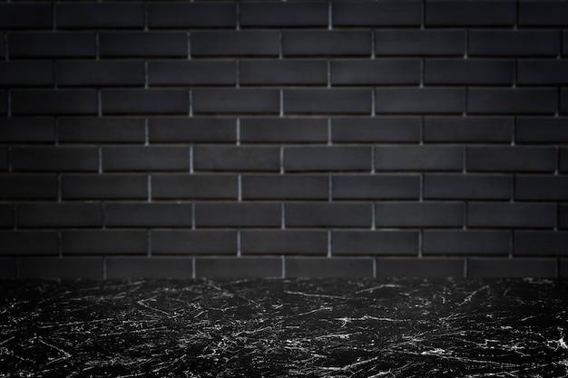 Muro di mattoni grigio scuro con il fondo del prodotto del pavimento di marmo nero