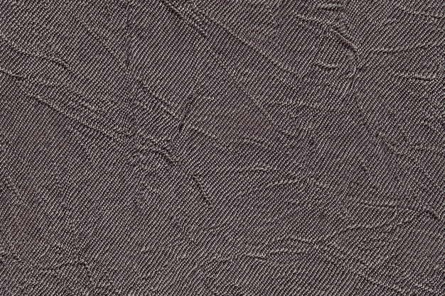 Dark gray wavy background from a textile material. fabric with fold texture closeup.