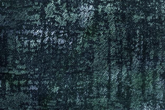 柔らかくふわふわの生地の濃い緑と青のふわふわの背景。エメラルドテキスタイルの質感