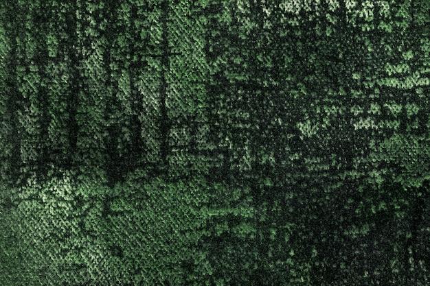 부드럽고 양털 같은 직물의 짙은 녹색과 올리브 솜털 배경. 에메랄드 벨벳 섬유의 질감