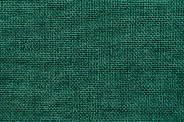 Dark green background of dense woven bagging fabric, closeup. structure of the textile macro.