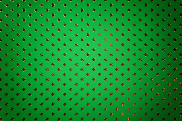 Dark green background from metal foil paper with a golden stars
