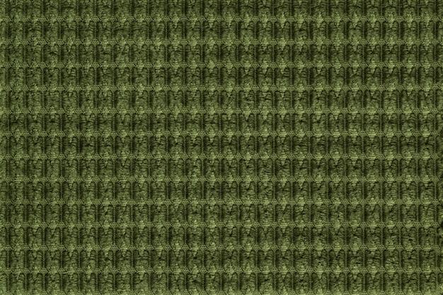 柔らかいフリース生地から濃い緑色の背景をクローズアップ。テキスタイルマクロのテクスチャ