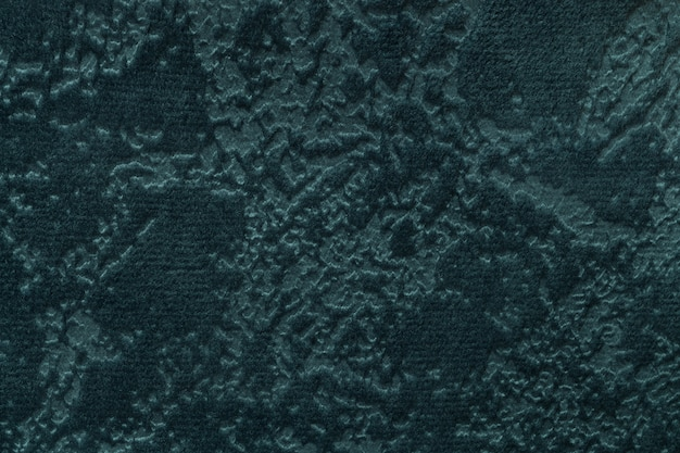 Dark green background from a soft upholstery textile material, closeup.