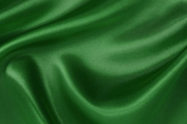 ダークグリーンの生地テクスチャ背景、シルクやリネンのしわくちゃのパターン。