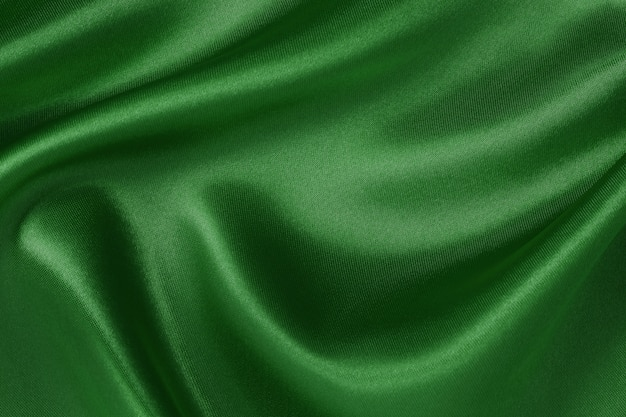 Dark green fabric texture background, crumpled pattern of silk or linen.