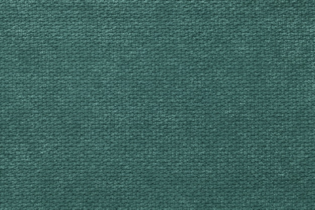 Dark green fluffy background of soft, fleecy cloth. texture of light nappy textile, closeup.