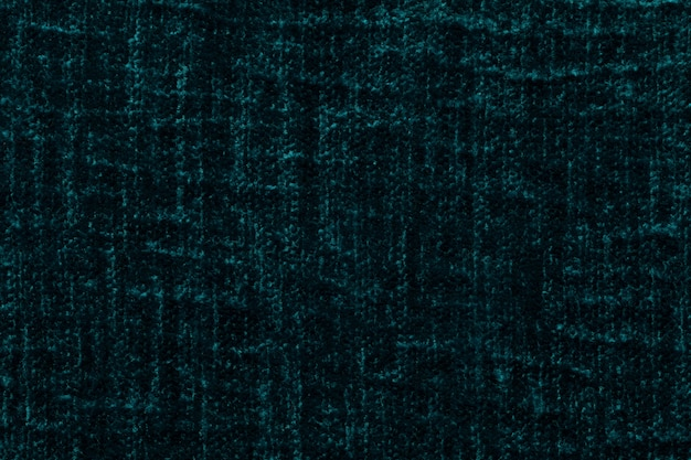 Dark green fluffy background of soft, fleecy cloth. texture of plush furry textile, closeup.