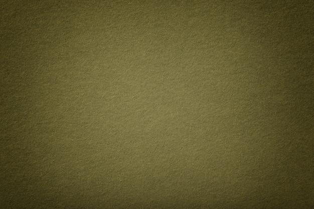 Dark green matt suede fabric closeup. velvet texture of felt.