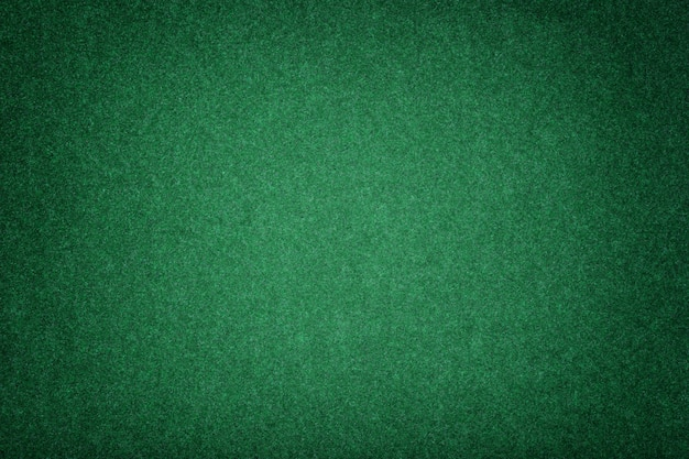 Dark green matt suede fabric closeup. velvet texture of felt.
