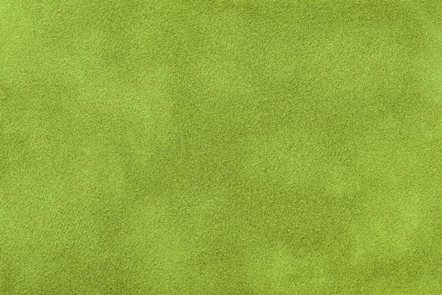 スエード生地の濃い緑色のマットな背景、クローズアップ。シームレスオリーブテキスタイル、マクロのベルベットの質感。カーキ色のフェルトキャンバスの背景の構造。