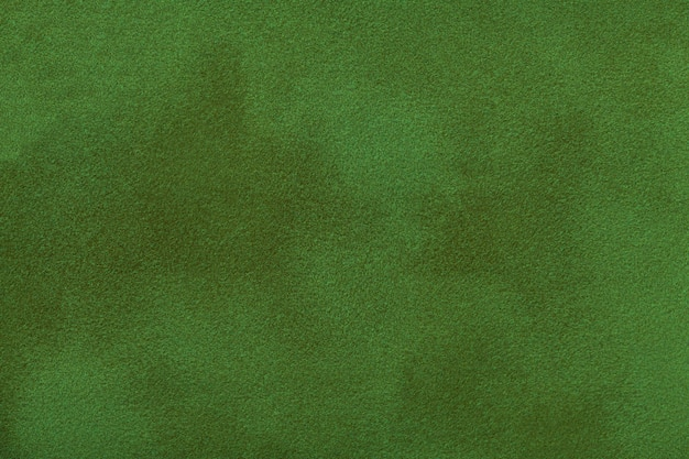 Dark green matte background of suede fabric, closeup.