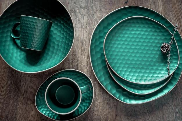 ダークグリーンのモダンなセラミック皿セット:2つのマグカップ、木製の背景にさまざまな形とサイズのいくつかのプレート。プレートにコーンが付いているカラマツの乾燥した小枝。クリスマスのテーブルデコレーション。上面図