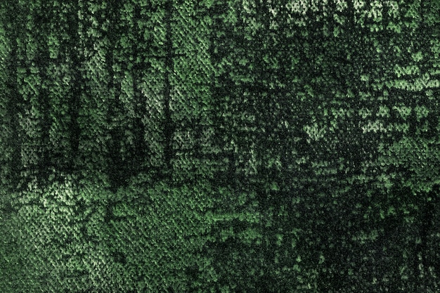 Dark green and olive fluffy background of soft, fleecy fabric. texture of emerald velveteen textile Premium Photo