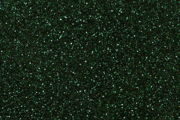 Dark green sparkling background from small sequins, closeup. brilliant backdrop.