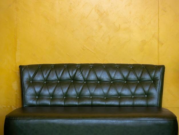 コピースペースのあるリビングルームの黄色の壁の背景にピンとボタンが付いたダークグリーンのヴィンテージレザーソファシート。