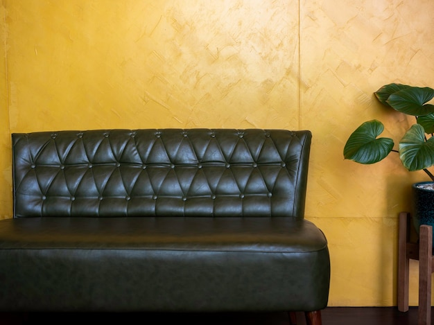 Dark green vintage leather sofa seat with pins and buttons near plant pot decoration on yellow wall background in the living room with copy space.