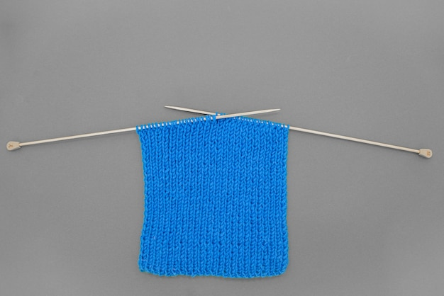 Dark grey background with bright blue knitted  scarf with knitting needles